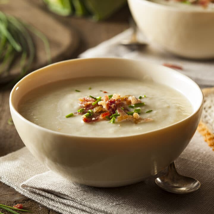 Instant Pot Potato Soup with leeks in a cream bowl and garnished with chives and bacon.
