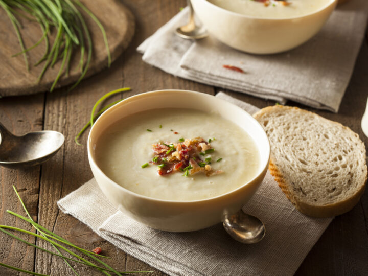 Creamy Potato and Leek soup garnished with chives and bacon. Top down view. Served in a cream-colored bowl on a rustic table.