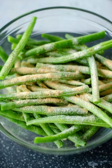 Green beans in a bowl sprinkled with the seasonings before tossing them. After this they can be transferred to the air fryer.