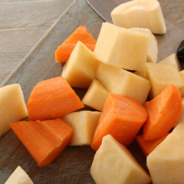 Raw Carrot and Potato Chunks cut into evenly sized pieces ready for seasoning and roasting.