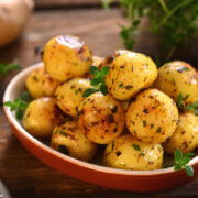 Roasted Baby Potatoes with herbs served in a red bowl.