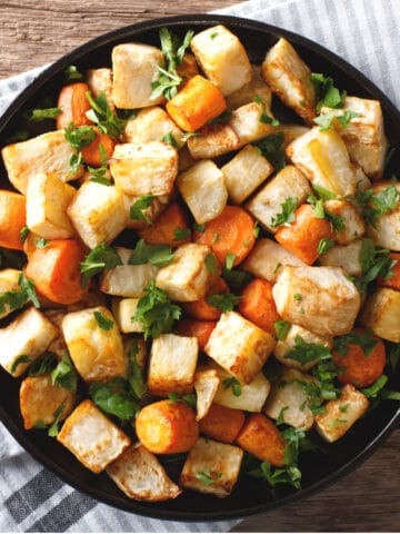 Roasted carrots and potatoes served in a bowl garnished with herbs. Top down view.