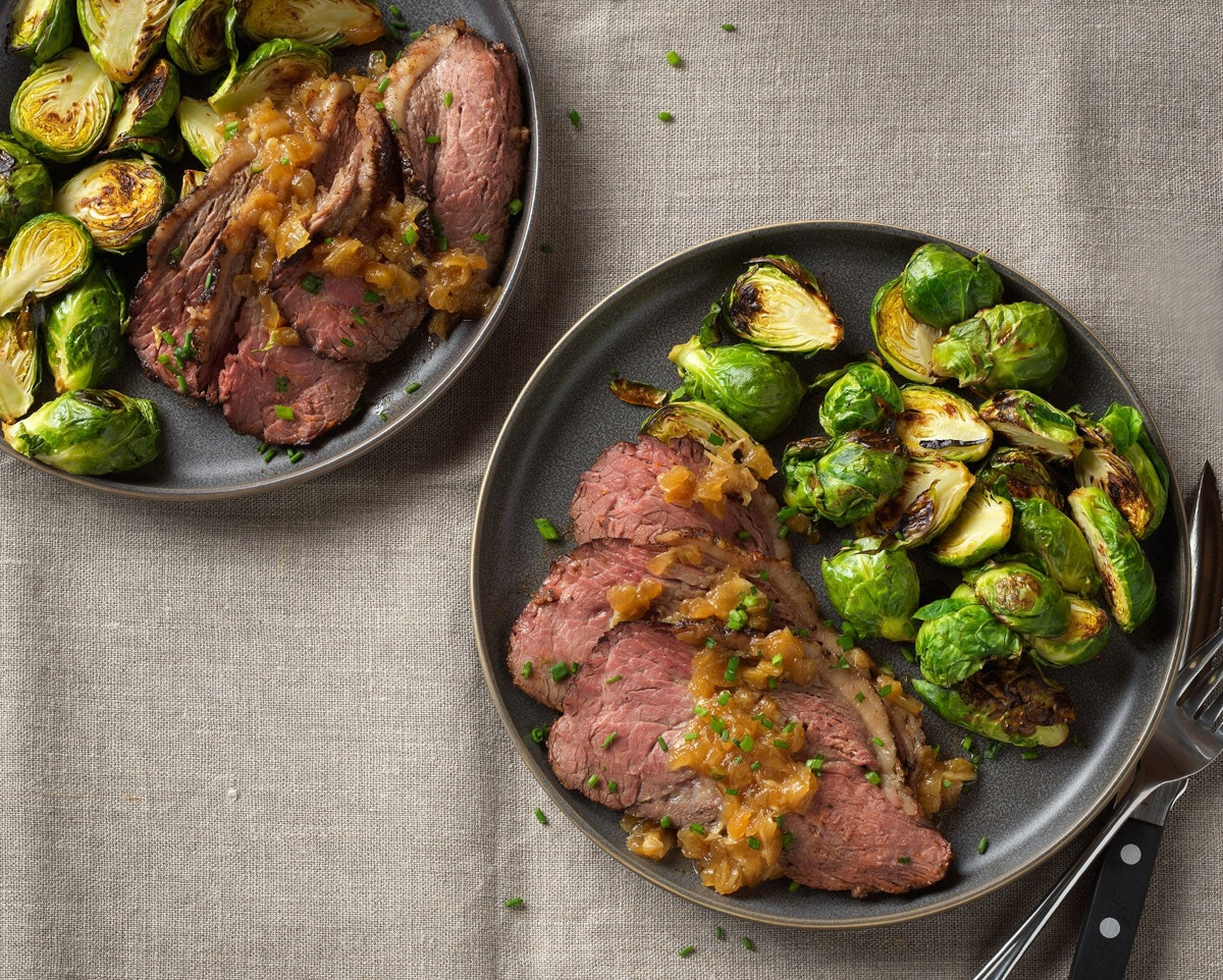 slices of homemade tender beef with brussels sprouts top down view