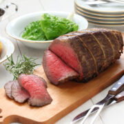 Carved rump roast on a wood carving board with a bowl of greens ready to be served.