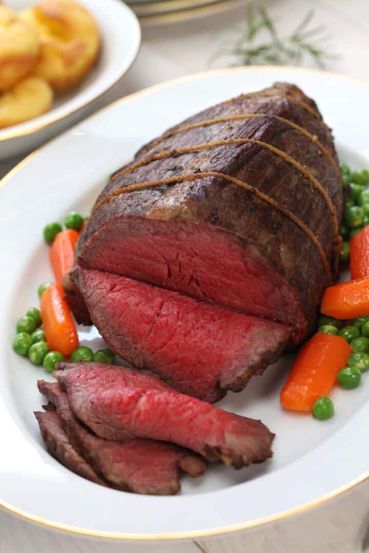 Slice Medium-rare Rump Roast on a white serving platter