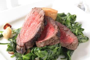 Carved Rump Roast on a bed of fresh spinach