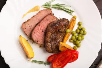 Slice rump roast served on a plate with vegetables on the side.