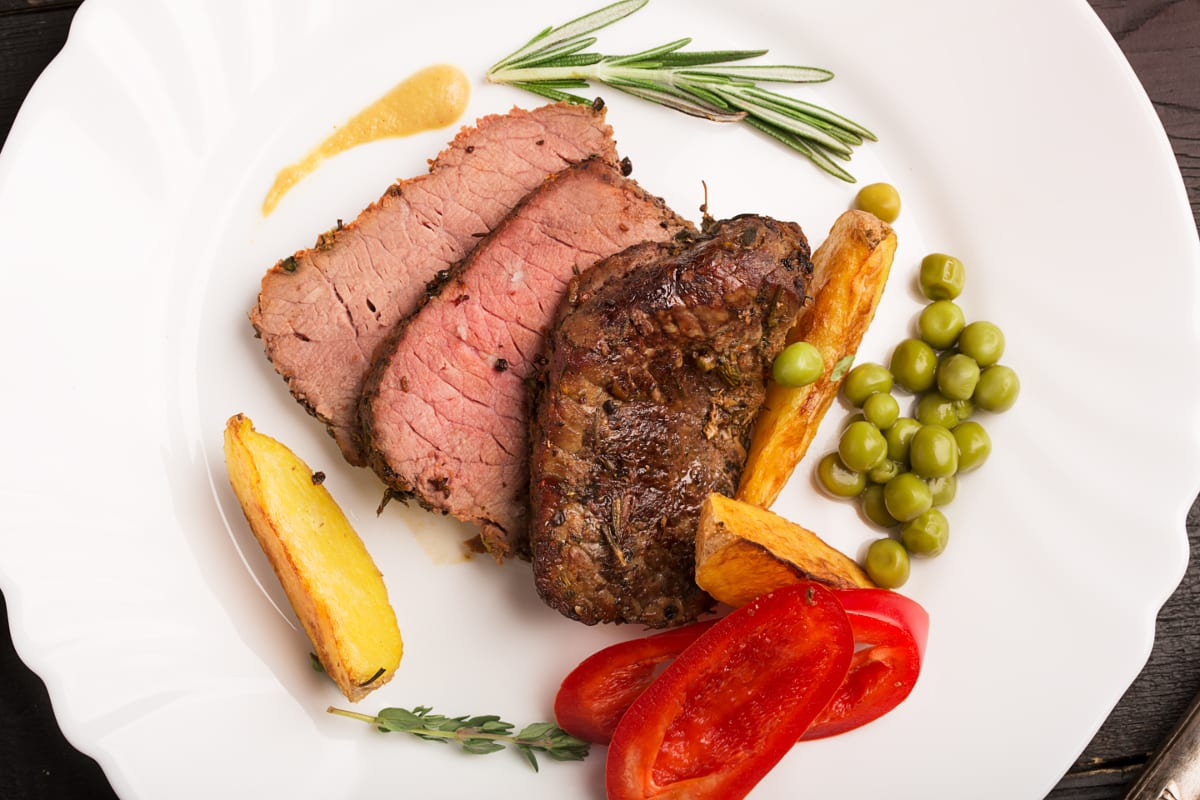 Sliced rump roast served on a plate with vegetables on the side.
