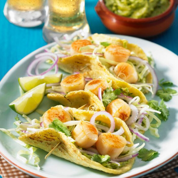 Pan Seared Scallops are wrapped in tortillas with a vegetable slaw and avocado sauce