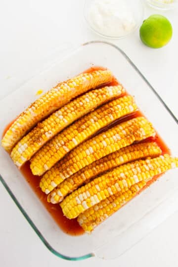 corn fries in a glass baking dish seasoned with bloody Mary mix and sprinkled with chili lime seasoning