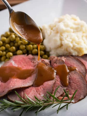 sirloin tip roast carved on a plate served with potatoes and peas. gravy drizzled over roast with a spoon.