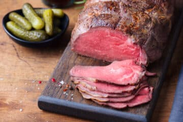 sirloin tip roast getting sitting on a cutting board carved into thin slices with a bowl of gherkins on the side
