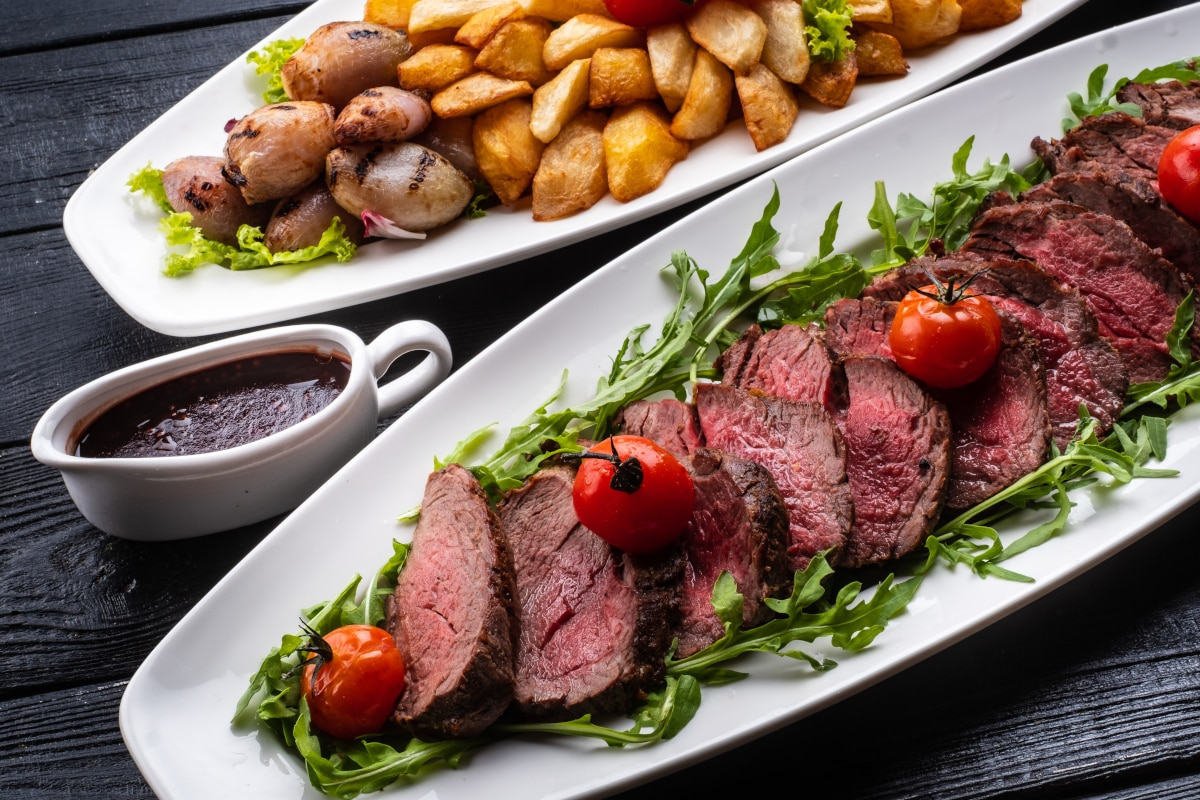 carved sirloin tip roast on an elongated white oval platter with a side dish of roasted potatoes also on a white long platter