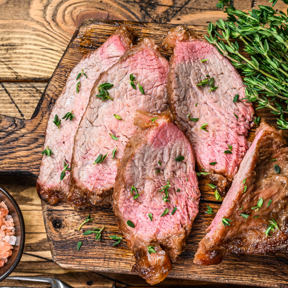slices of tri tip on a board with herbs