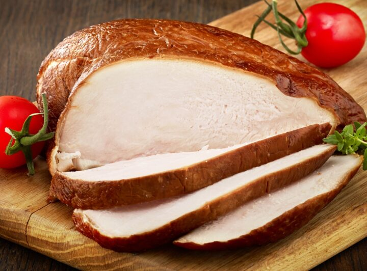 Sliced whole smoked chicken breast showing crispy skin and tender juicy meat that is no longer pink in the inside.