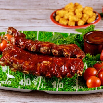 Slow cooker ribs on football themed serving tray with air fryer tater tots and extra barbecue sauce