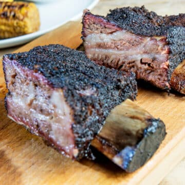 closeup of two smoked beef ribs on a wooden carving board