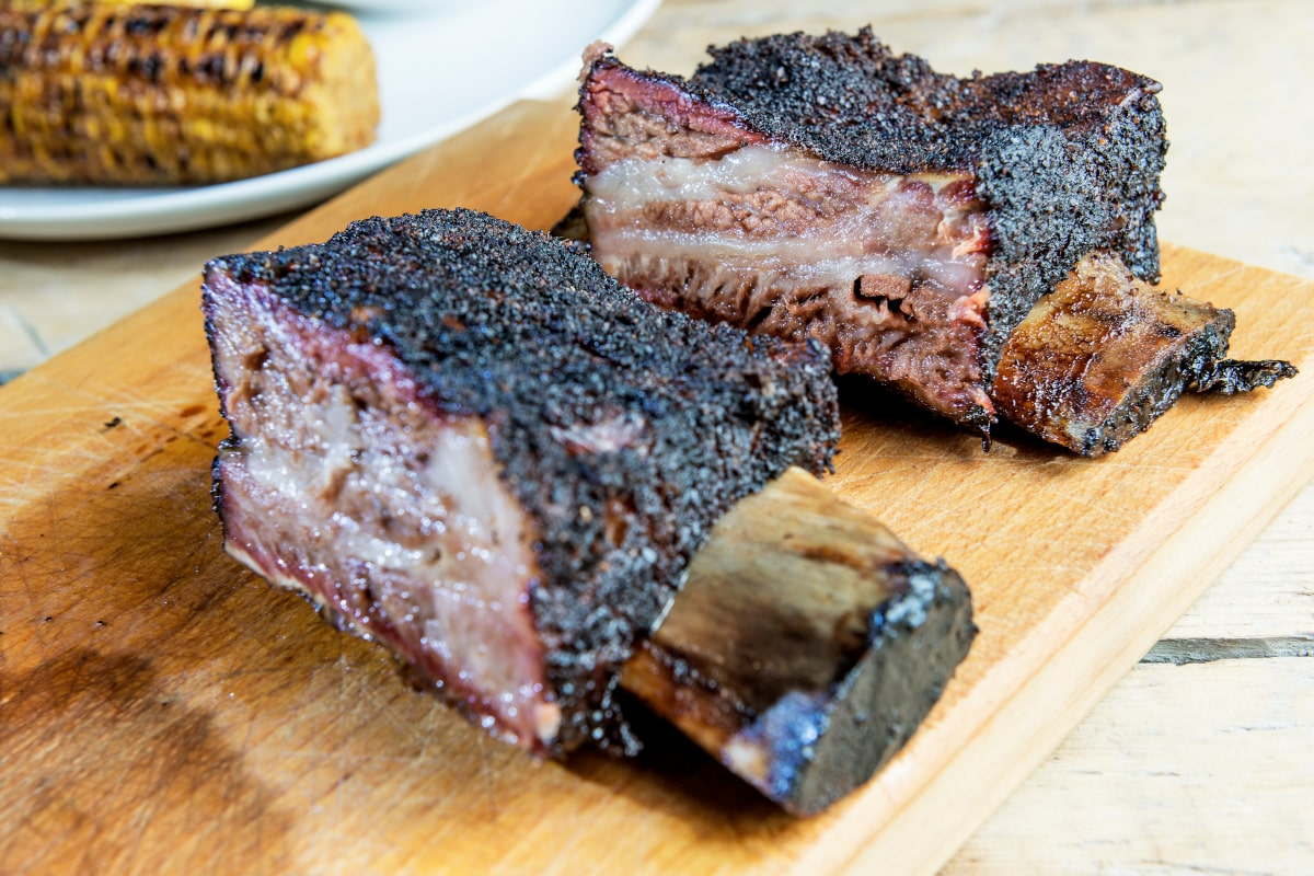 close up photo of two beef ribs cut on a wooden board