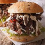 smoked chuck roast pulled and served on a bun. sandwich is drizzle with horseradish cream sauce.