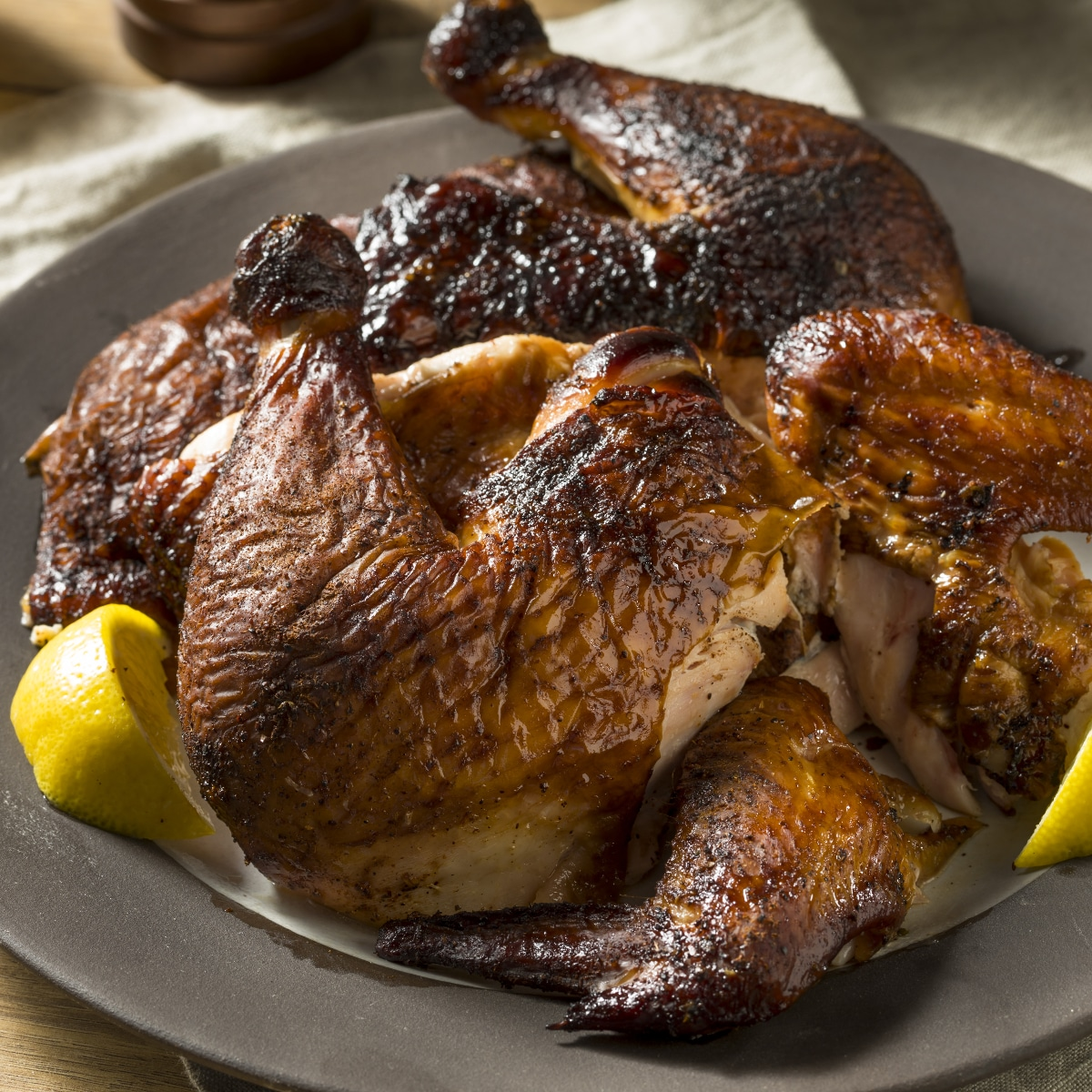 Smoked Whole Chicken carved and arranged on a serving platters. The chicken parts are browned and seasoned.