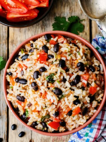 Spanish black beans and rice in a bowl on a wooden table.