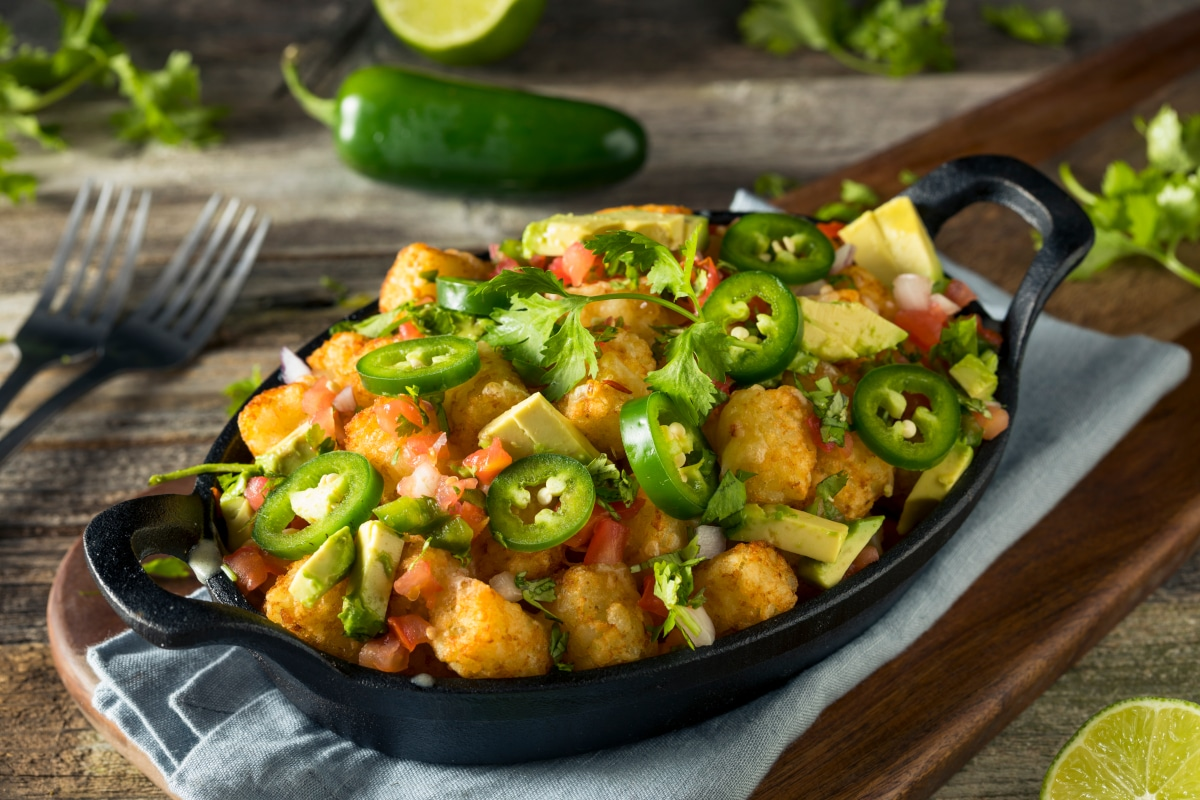 air fry tater tots with sliced jalapenos, cheese, and cilantro in a skillet on a table.