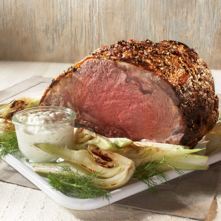 Top round roast on a white serving platter with horseradish sauce on the side