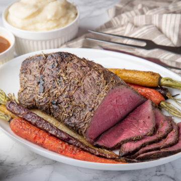 Top round roast carved on white serving platter with roasted carrots alongside ready to serve.