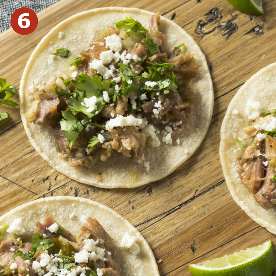 Corn tortillas topped with pulled pork, fresh cilantro, cotija. Carnitas are ready to be served with limes and salsa