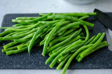 Trimmed green beans on a black cutting board.