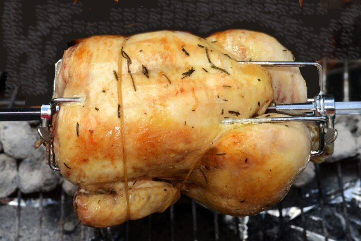 Trussed Chicken on a Rotisserie grill showing compact chicken with golden brown color