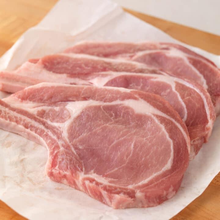 Raw bone-in pork chops ready for pan frying.