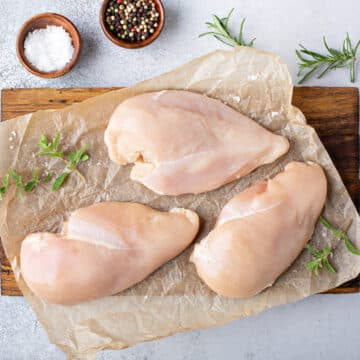 Raw chicken breasts on on work surface with seasonings ready to pressure cook.